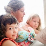 Kids reading to grandmother